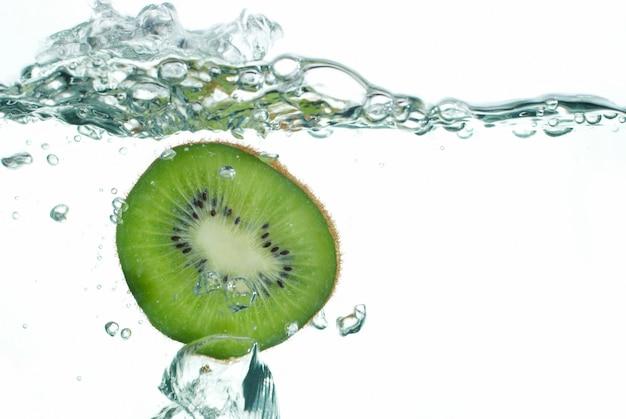 Frische kiwi, die ins wasser springt