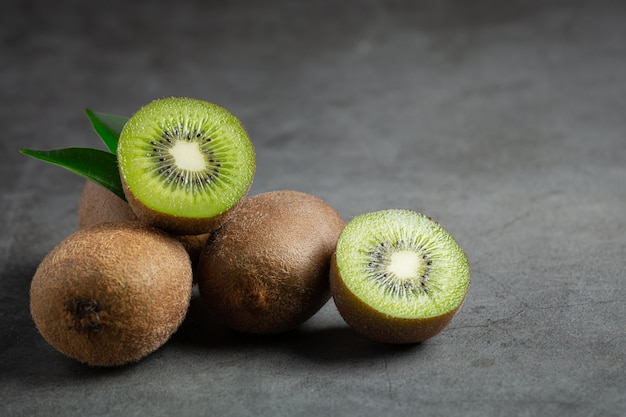 Frische kiwi, halbiert, auf dunklen boden legen