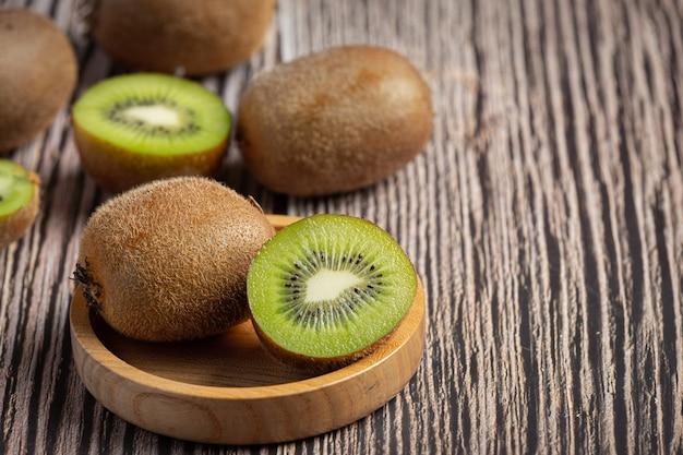 Frische kiwi, halbiert, auf eine holzschale stellen