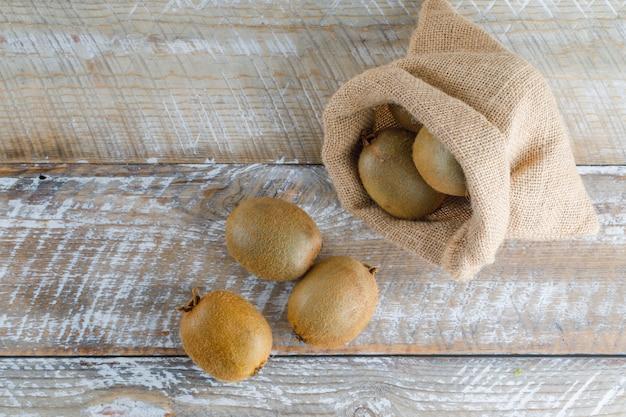 Frische kiwi in einem sack auf einem holztisch. flach liegen.