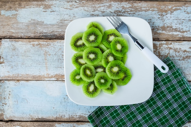 Frische kiwi in einer platte auf einem holztisch