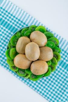 Frische kiwi in einer platte mit getrockneter kiwi-draufsicht auf weißem und picknickstoffhintergrund