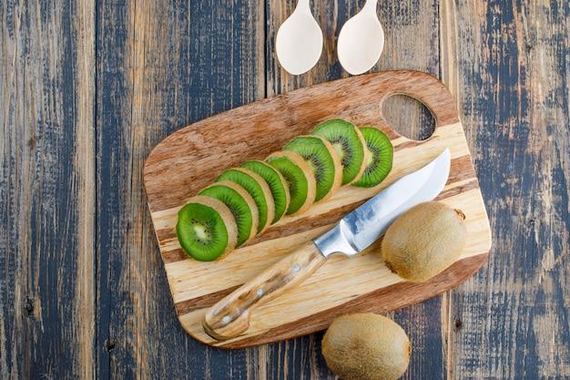 Frische kiwi mit messer, löffel auf holz- und schneidebretthintergrund, draufsicht.