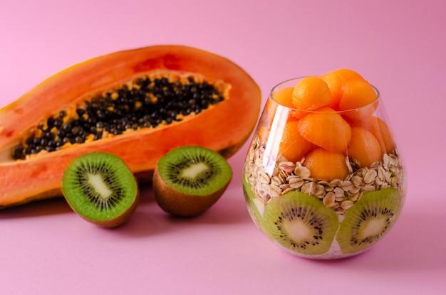 Frische kiwi, papaya und haferflocken zum gesundes frühstück auf purpur