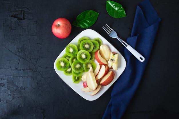 Frische kiwi und äpfel der mischfrucht mit trauben in einer platte auf einem holztisch.