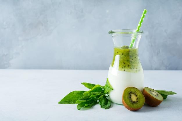 Frische kiwi- und spinat-kirsch-smoothies in einem glas auf hellem betonhintergrund. gesunde ernährung, entgiftung, diätkost