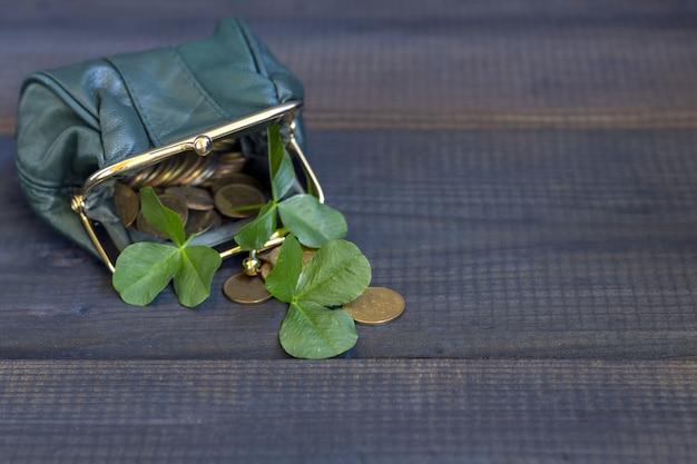 Frische kleeblätter und goldmünzen kommen aus einer grünen handtasche auf einem dunklen tisch