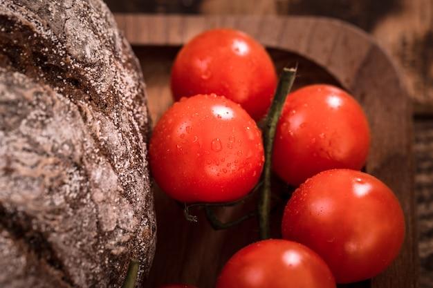Frische kleine bio-tomaten auf einer holzplatte nahaufnahme