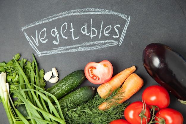 Frische köstliche bestandteile für das gesunde kochen oder salat, die auf draufsicht der rustikalen oberfläche, fahne machen. diät oder vegetarisches nahrungsmittelkonzept.