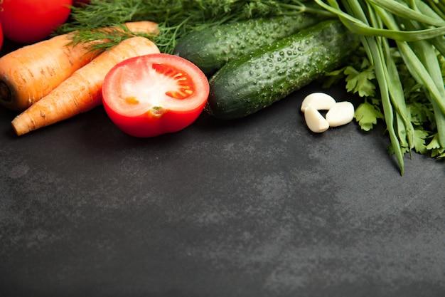 Frische köstliche bestandteile für das gesunde kochen oder salat, die auf rustikalem hintergrund, draufsicht, fahne machen. diät oder vegetarisches nahrungsmittelkonzept.