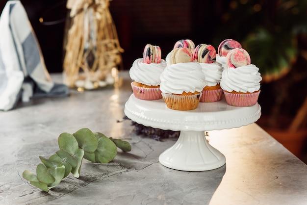 Frische köstliche cupcakes mit weißer sahne und farbigen macarons auf einem weißen tablett auf marmortisch.