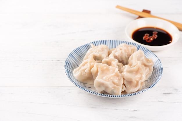 Frische, köstliche gekochte schweinefleisch-gyoza-knödel, jiaozi auf weißem hintergrund mit sojasauce und stäbchen, nahaufnahme, lebensstil. selbstgemachtes designkonzept.