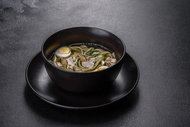 Frische köstliche heiße suppe mit nudeln und wachtelei in einem schwarzen teller