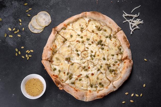Frische köstliche italienische pizza mit birnen- und kürbiskernen auf dunklem betonhintergrund. italienische küche