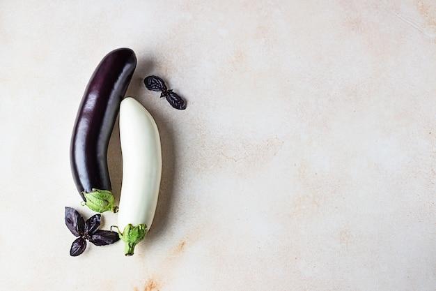 Frische köstliche weiße und lila auberginen mit lila basilikum. draufsicht.