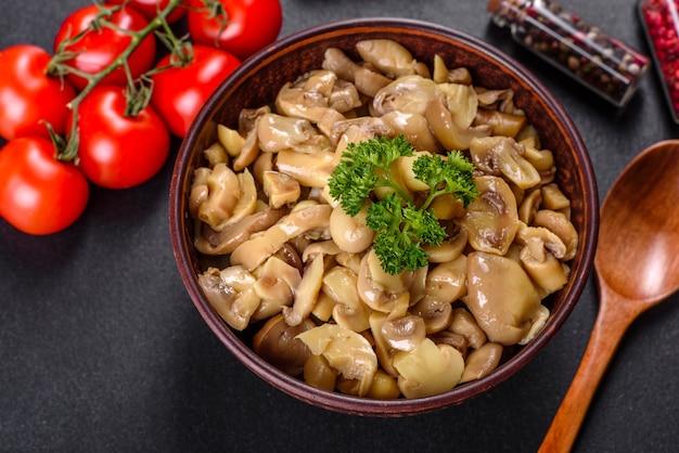 Frische köstliche würzige dosenpilze mit gewürzen und kräutern in keramikschalen auf einem dunklen betonhintergrund