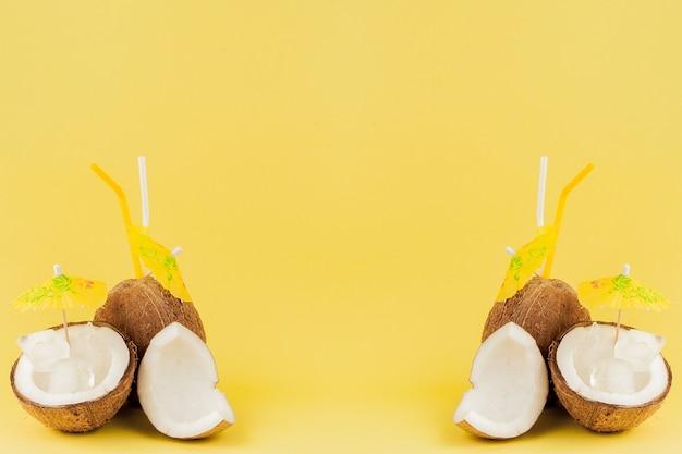 Frische kokoscocktails mit plastikstrohhalmen auf gelbem hintergrund mit kopierraum