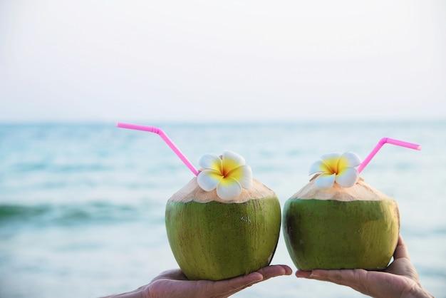 Frische kokosnuss in den paarhänden mit dem plumeria verziert auf strand mit seewelle - flitterwochenpaartourist mit sonnenferienkonzept der frischen frucht und des meersands