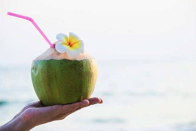 Frische kokosnuss in der hand mit dem plumeria verziert auf strand mit seewelle - tourist mit sonnenferienkonzept der frischen frucht und des meersands