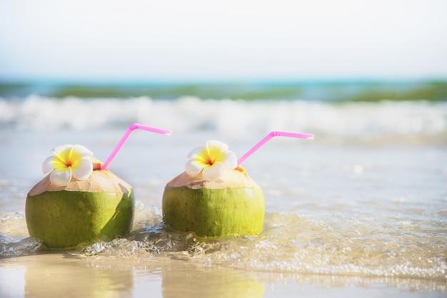 Frische kokosnuss mit der plumeriablume verziert auf sauberem sandstrand mit seewelle - frische frucht mit meersandsonnen-ferienkonzept