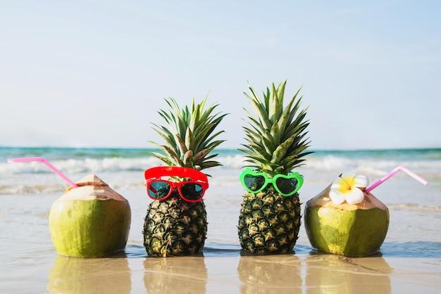 Frische kokosnuss und ananas setzten reizende gläser der sonne auf sauberen sandstrand mit seewelle - frische frucht mit meersandsonnen-ferienkonzept