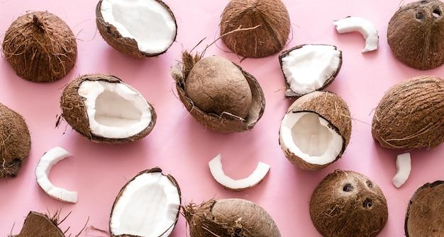 Frische kokosnusshälften auf einem rosa hintergrund, pop-art-design. draufsicht, nahaufnahme, kreatives konzept