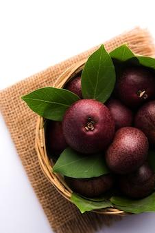 Frische kokum- oder garcinia-indica-frucht aus indien isoliert über weiß oder in zuckerrohrkorb mit blättern. selektiver fokus