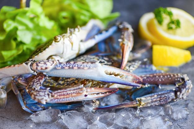 Frische krabben für gekochtes essen im restaurant oder meeresfrüchte-markt / raw krabben auf eis mit gewürzen zitrone und salat salat auf dem dunklen teller hintergrund blaue schwimmkrabbe