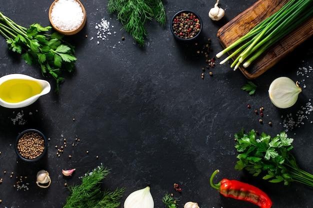 Frische kräuter, gewürze, paprika, dill, petersilie auf schwarzem hintergrund. platz für text, kulinarisches konzept. hintergrund für menü, rezept.