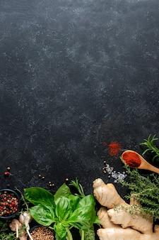 Frische kräuter, kräuter, ingwer und gewürze auf einem schwarzen hintergrund mit kopierraum. kulinarisches konzept.