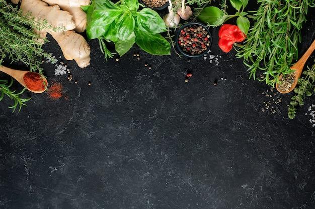 Frische kräuter, kräuter und gewürze auf einem schwarzen hintergrund mit kopierraum. kulinarisches konzept.
