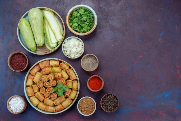 Frische kürbisse mit gemüse und gewürzen aus der draufsicht auf dem dunkelvioletten schreibtischfleisch-abendessen-gemüsemehl