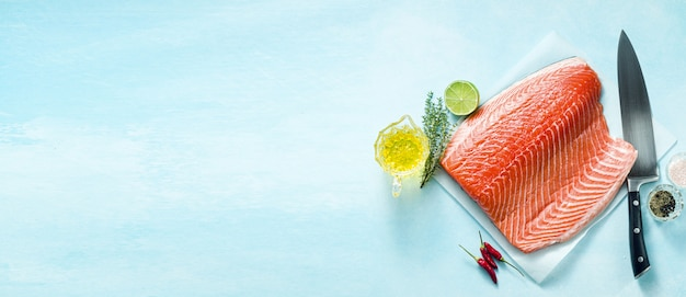 Frische lachsscheibe auf einem hölzernen schneidebrett mit einem kochmesser auf dem tisch. kochrezept. lebensmittelhintergrund. frische fischprodukte