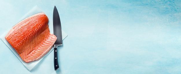 Frische lachsscheibe auf einem hölzernen schneidebrett mit einem kochmesser auf dem tisch. kochrezept.