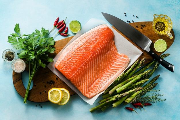 Frische lachsscheibe auf einem holzschneidebrett mit frischen aromatischen kräutern und spargel auf dem tisch. kochrezept. lebensmittelhintergrund. frische fischprodukte
