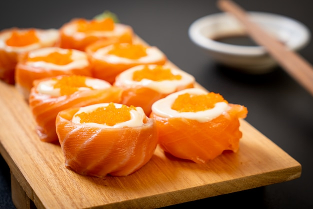 Frische lachssushi-rolle mit mayonnaise und garnelenei