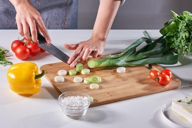 Frische lauchscheiben in die hände einer köchin auf einem holzbrett auf dem küchentisch um eine vielzahl von bio-gemüse geschnitten. gesunden salat kochen