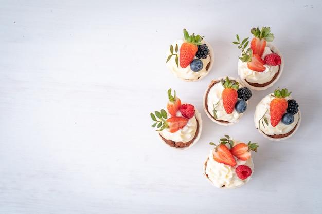 Frische, leckere cupcakes mit joghurtcreme, frischen beeren. muffin mit sahne.