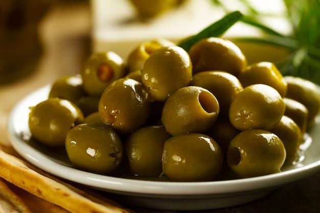 Frische, leckere griechische grüne oliven mit grissini und frischem rosmarin <. nahansicht. mediterranes essen.