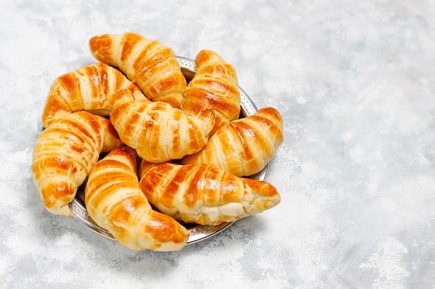 Frische leckere hausgemachte croissants auf grau-weiß. französisches gebäck