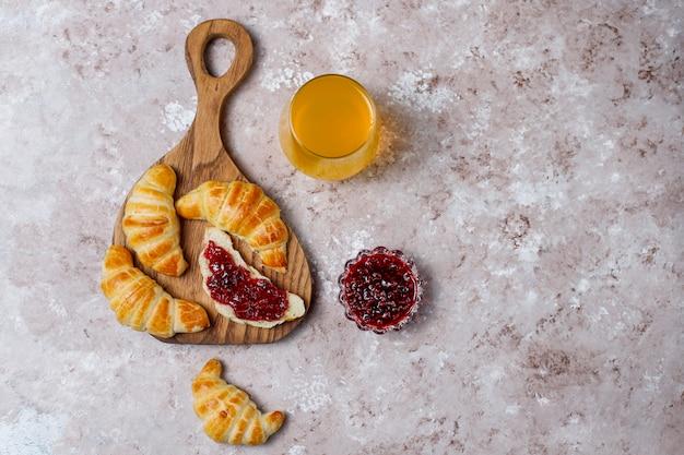 Frische leckere hausgemachte croissants mit himbeermarmelade auf grau-weiß. französisches gebäck