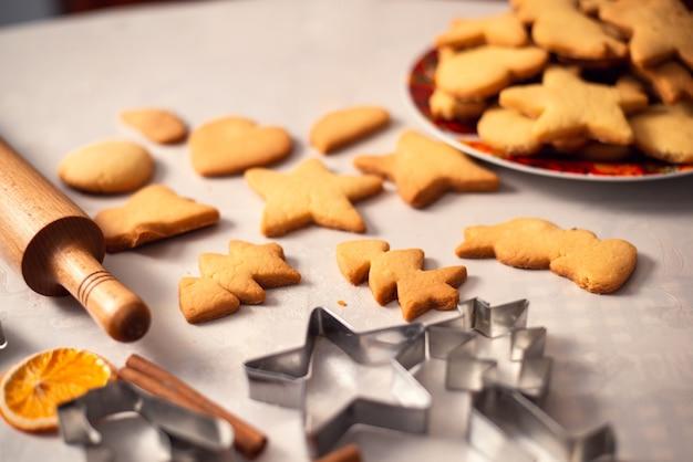 Frische leckere kekse in verschiedenen formen in der nähe von nudelholz und metallformen auf dem tisch