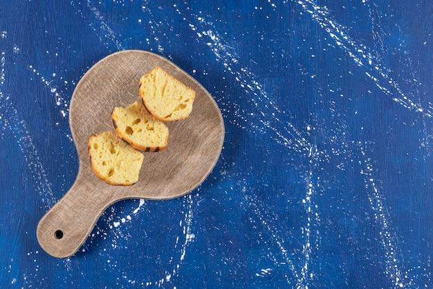 Frische leckere kuchen in scheiben auf holzbrett gelegt.