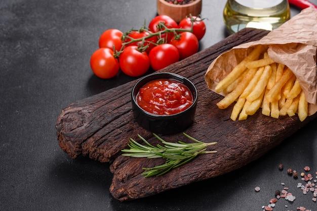 Frische leckere pommes frites und rote sauce auf einem holzschneidebrett. ungesundes essen, fast food
