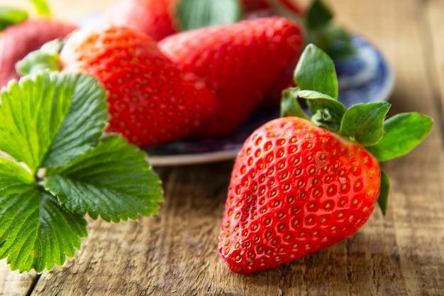 Frische, leckere sommer-erdbeere. reife erdbeere auf holzbrett hautnah. sommer tag licht.
