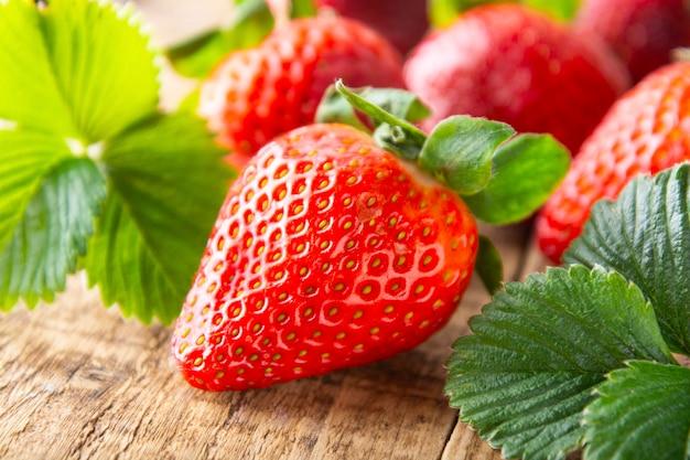 Frische, leckere sommererdbeere. nahaufnahme reife erdbeere auf holzbrett. sommertageslicht.