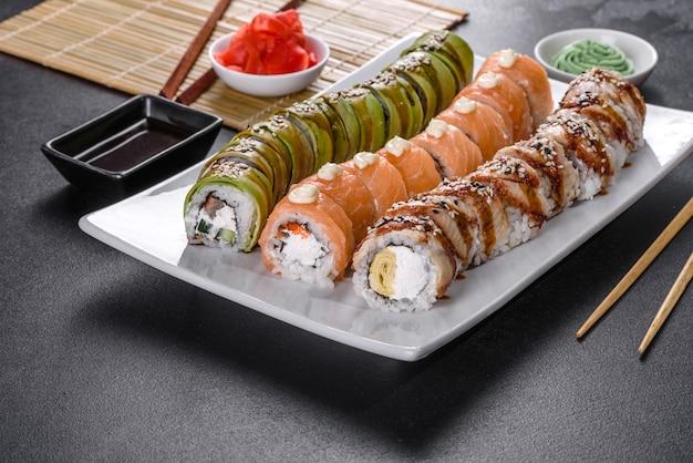 Frische leckere sushi-rollen in form eines drachen mit ingwer und wasabi. japanische küche