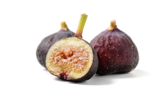 Frische lila feigenfrüchte und scheiben, die auf weißer oberfläche isoliert sind. feigen sind reich an kalzium und enthalten antioxidantien. sie verhindern verstopfung und lindern diabetes.