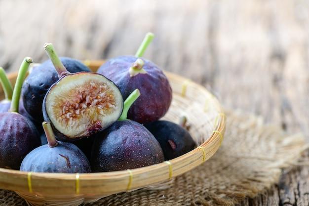 Frische lila feigenfrüchte und scheiben, die im bambuskorb auf altem holz isoliert sind. feigen sind reich an kalzium und enthalten antioxidantien. sie verhindern verstopfung und lindern diabetes.