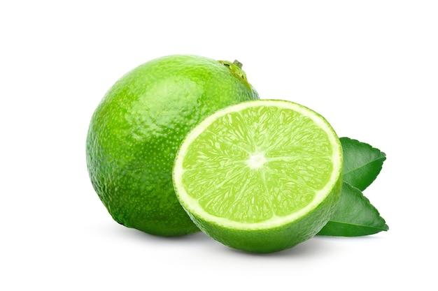 Frische limette mit halbiertem schnitt und grünem blatt lokalisiert auf weiß